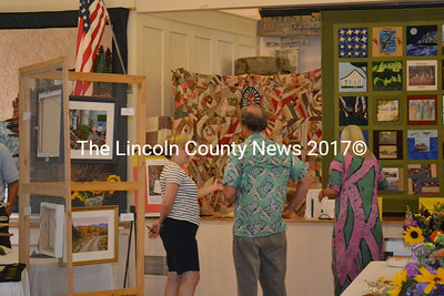 Westport Island's signature quilt (left), made in 1886 by Westport Island women, and a 2010 quilt made to honor Lincoln County's 250th birthday are admired during a reception celebrating the 60th anniversary of the Westport Community Association. (Charlotte Boynton photo)
