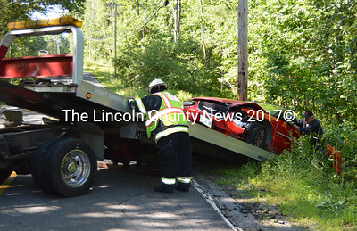 Assisted by Waldoboro Assistant Fire Chief Bill Maxwell (left), tow truck operator Gary Lane, of Hillside Collision, prepares to load a damaged Chrysler convertible onto a flatbed trailer after a single-vehicle accident in Waldoboro Thursday, Aug. 13. (Sherwood Olin photo)
