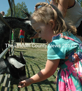 Monica Jones makes a friend at the petting zoo on Saturday, Aug. 15. Due to a fundraising event in the spring and sponsors, the petting zoo was one of the free attractions at Olde Bristol Days. (Maia Zewert photo)