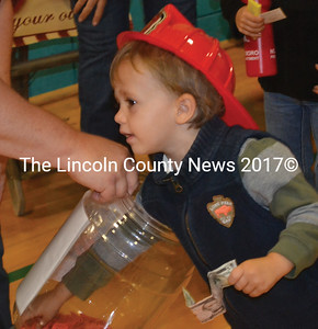 Masen Michaud reaches for a winning ticket for the apple pie door prize at the Nobleboro AppleFest. (Alexander Violo photo)