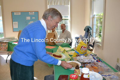 Sally Howe adds sauerkraut and other fixings to her bratwurst during Oktoberfest at Wiscasset First Congregational Church on Saturday, Oct. 3. (Charlotte Boynton photo)