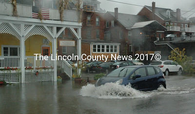 A driver braves foot-deep water in the Damariscotta municipal parking lot Sept. 30. Town manager Matt Lutkus said the water was unable to drain due to high tide. (Maia Zewert photo)