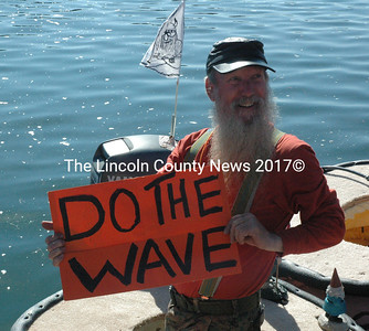 Tom Lishness lead the crowd in the wave during the Pumpkinboat Regatta held Monday, Oct. 12. Lishness later would go on to take third place in the powerboat division. (Maia Zewert photo)
