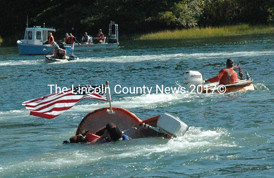 Tom Lishness speeds ahead as Jeff Dutra's boat overturns in the Damariscotta Harbor Oct. 12. The annual pumpkinboat regatta drew thousands to the harbor to watch the event. (Maia Zewert photo)