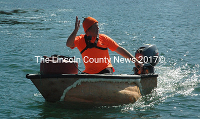 Damariscotta Pumpkinfest and Regatta co-founder Buzz Pinkham waves to the announcers before the powerboat divison race Oct. 12. Pinkham won second place in the event. (Maia Zewert photo)