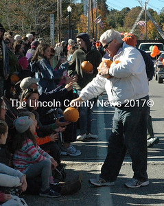 Walter Hilton handed out pumpkins to members of the crowd on behalf of Clark's Farms during the parade Saturday, Oct. 10. (Maia Zewert photo)
