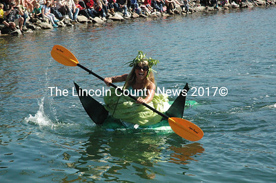 "Jaja Martin navigates her Yoda-inspired pumpkin while wearing a bright green prom dress during the pumpkinboat regatta Oct. 12. ""I was afraid it wasn't going to fit in the pumpkin at first,"" Martin said."