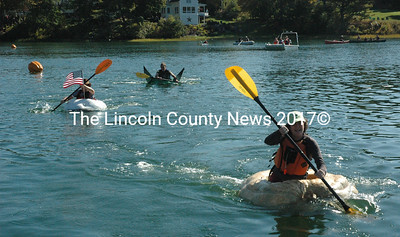 Lisa Evans handly defeats Jason Douglass and Robert Watts in the first heat of the paddle division of the pumpkinboat regatta Oct. 12. The regatta capped off a week's worth of celebration of the annual Damariscotta Pumpkinfest. (Maia Zewert photo)