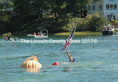 Jeff Dutra waves the American flag to the cheering crowd after tipping his boat during the pumpkinboat regatta in the Damariscotta Harbor Oct. 12. (Maia Zewert photo)