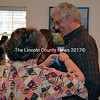 """Fran Roberts pins a """"60"""" ribbon on Lincoln County News Publisher Chris Roberts as he enters a surprise 60th birthday party at the Damariscotta River Grill Thursday, Oct. 22. The party was attended by family, friends, and several longtime clients, as well as the entire LCN staff. (J.W. Oliver photo)"""