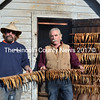 Brothers Todd (left) and Ken Lincoln hold strings of freshly smoked herring outside the smokehouse next to the S Road School in South Bristol Friday, Nov. 13. The Lincolns smoke herring in the old smokehouse about once a year to keep a long-standing local tradition alive. (J.W. Oliver photo)