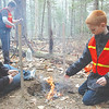Steven Ward, David Gagnon, and Cason Gifford, left to right, work on keeping the fire alive during the outdoor elective, taught by Great Salt Bay Community School Assistant Principal Ira Michaud Nov. 19. During the twice-weekly elective, Michaud teaches the students wilderness skills like fire building, knot tying, and animal tracking. (Maia Zewert photo)