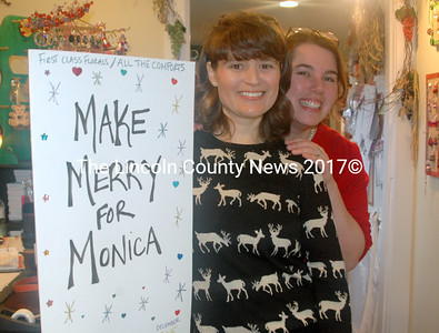 Heather Hilton Clark (left) made the huge card signed by the guests on Saturday. Aubrey Martin (right), owner of The Animal House, with Andrea Parker (not pictured) were the driving forces of the Making Merry for Monica mob Dec. 12. (Eleanor Cade Busby photo)