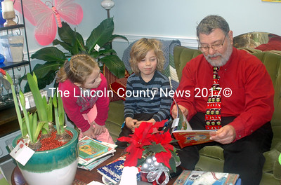 Grace Bryant and Eli Jones listen as Nick Azzaretti reads Christmas and Hanukkah stories at the Making Merry for Monica Event on Saturday, Dec. 12.  (Eleanor Cade Busby photo)