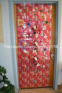 Wiscasset Treasurer Shari Fredette decorated her door at the town office as a large Christmas present, with hanging Santa Claus dolls. As of Monday, Dec. 21, her door had received one of three votes cast. (Charlotte Boynton photo)