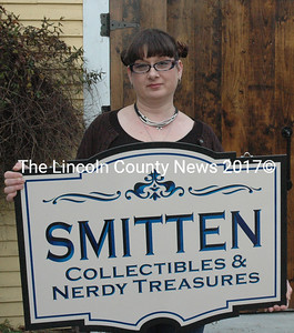 Susan Chalmers holds the sign for her store, Smitten: Collectibles & Nerdy Treasures. Chalmers has operated an eBay store to sell her collectibles since 2008 and will open a brick-and-mortar location in Damariscotta in the spring. (Maia Zewert photo)