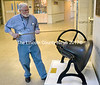 """Bill """"Mr. Bill"""" Howard, demonstrates his daily ringing of a 104-year-old bell in the entryway of Jefferson Village School. Howard, the school's technology coordinator, has a ritual of ringing the bell when he arrives around 7:30 a.m. each morning. (D. Lobkowicz photo)"""