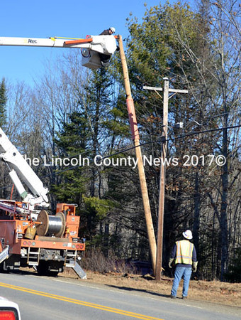A Central Maine Power crew adjusts a pole knocked out of place during an accident on Washington Road in Jefferson. The pole was smoldering where it contacted a power line. (D. Lobkowicz photo)