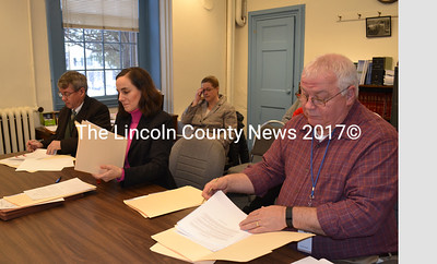 From left, Lincoln County Administrator John O'Connell, Bernstein Shur attorney Shana Mueller, representing Camden National Bank; and Lincoln County Treasurer Rick Newell prepare paperwork for a tax anticipation note for the Lincoln County Board of Commissioners during the board's meeting Jan. 19. (Charlotte Boynton photo)
