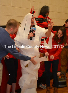 WGME News 13 anchor Jeff Peterson is given a taste of Wiscasset's school spirit as he is covered with toilet paper during the school spirit challenge pep rally Jan. 22. Principal Peg Armstrong is pictured in the backround duct-taped to a wall. (Abigail Adams photo)