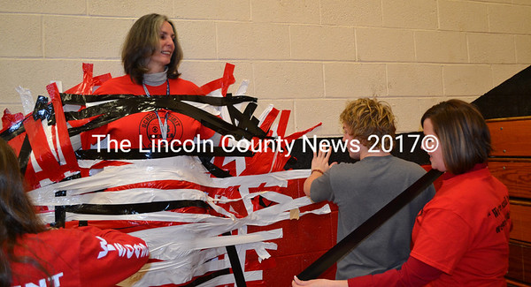 Superintendent Heather Wilmot (far right) waits her turn to help in the effort to duct tape Wiscasset Middle High School Principal Peg Armstrong to the wall at the school's spirit challenge pep rally Jan. 22. (Abigail Adams photo)