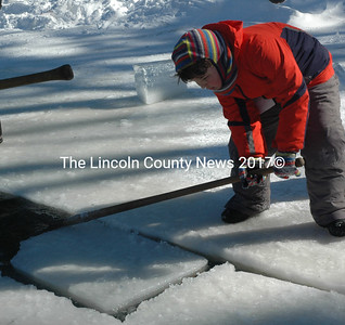 Nine-year-old Ethan Miranda, of Edgecomb, guides a block of ice along the channel during the annual ice harvest at the Thompson Ice House in South Bristol Sunday, Feb. 14. Volunteers of all ages were welcome to participate in the harvest and use antique ice-cutting tools. (Maia Zewert photo)