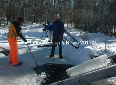 Volunteers prepare another block of ice as a pulley system transports a block up a ramp and into the Thompson Ice House in South Bristol during the annual ice harvest Sunday, Feb. 14. (Maia Zewert photo)