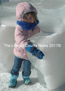 Maylin LeBlanc cuddles up to a piece of ice cut from Thompson Pond during the annual ice harvest held Sunday, Feb. 14. Attendees braved temperatures in the single digits to witness and participate in the ice harvest at the Thompson Ice House in South Bristol on Valentine's Day. (Maia Zewert photo)