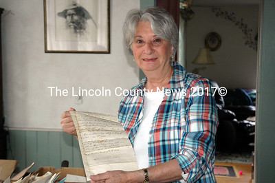 Mary Sue Weeks displays one of the historic town documents she found tucked away in the attic of her family's home in Bremen. (Alexander Violo photo)