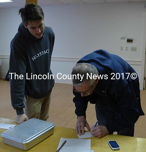 Lincoln Academy senior Camden Gulden (left) waits for an assignment from Robert Breckenridge, the faculty adviser for the Alpha Sigma Gamma service fraternity, at The Second Congregational Church in Newcastle on Monday, Jan. 18. (Maia Zewert photo)
