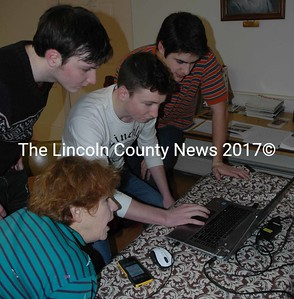 From left, Lincoln Academy students Kevin Fitzpatrick, Theo Seidel, and Mark Damon help Deb Arter transfer photos from her phone to her computer in The Second Congregational Church in Newcastle on Monday, Jan. 18. The students, all members of Alpha Sigma Gamma, performed a variety of odd jobs in Bremen, Damariscotta, Newcastle, Waldoboro, and Walpole in celebration of Martin Luther King Jr. Day. (Maia Zewert photo)