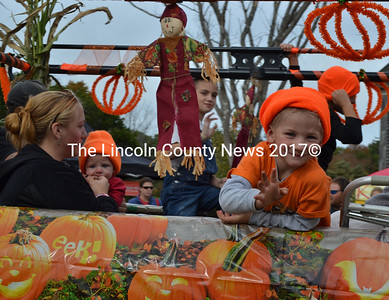 A child in the back of a Dennis Walsh Contractor truck waves to the crowd during the annual Giant Pumpkin Parade on Saturday, Oct. 8. (Maia Zewert photo)