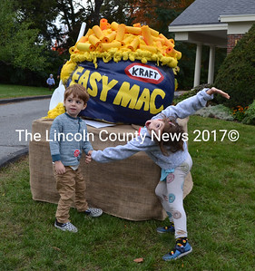 Inigo (left) and Fable Reese, of Miami, pose for a photo in front of a pumpkin resembling a bowl of macaroni and cheese. The Reese family traveled from Miami to Maine for the Damariscotta Pumpkinfest. (Maia Zewert photo)