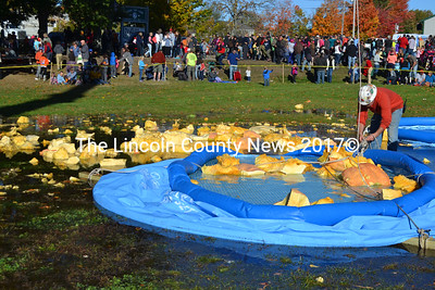 Damariscotta Pumpkinfest volunteer Curt Crosby cleans up after the pumpkin drop at Round Top Farm on Monday, Oct. 9. Giant pumpkins were dropped into two pools and onto a car from a height of approximately 145 feet. (Maia Zewert photo)