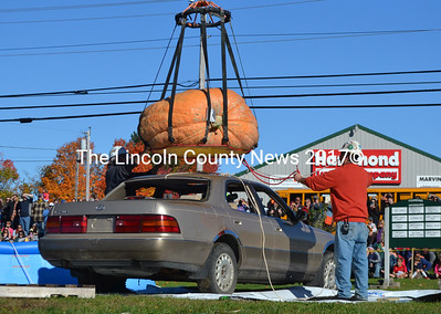 Bill Clark (left) and Curt Crosby position a giant pumpkin over a Lexus on Monday, Oct. 9. The pumpkin, which was grown by Crosby, was dropped  approximately 145 feet onto the car. (Maia Zewert photo)