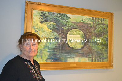 "Miles Memorial Hospital League Art Committee President Julie Babb stands before ""Sanctuary,"" an oil painting of the Benner Road Stone Arch Bridge over the Pemaquid River painted by and donated to LincolnHealth - Miles Campus by Damariscotta artist Bertil Whyman earlier this year. (Christine LaPado-Breglia photo)"