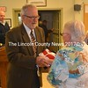 Retired Cmdr. Richard Tetrev presents the American flag that was flown at the Brunswick Naval Station on the 50th anniversary of D-Day to Wiscasset Board of Selectmen Chair Judy Colby on Tuesday, Oct. 18. (Abigail Adams photo)
