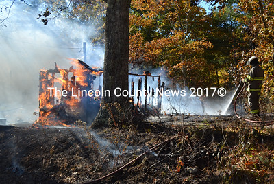 A Damariscotta firefighter sprays down a burning shed on North Dyer Neck Road in North Newcastle on Wednesday, Oct. 19. Firefighters from Newcastle, Damariscotta, Alna, and Nobleboro responded to the scene, and Wiscasset provided station coverage. (Maia Zewert photo)