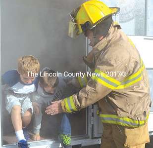 Bristol firefighter Daniel MacWalters helps Bristol Consolidated School students Ryan Foster (left) and James Wyman-Benner exit the Damariscotta Fire Department's educational smoke trailer at BCS on Wednesday, Oct. 19. (Maia Zewert photo)