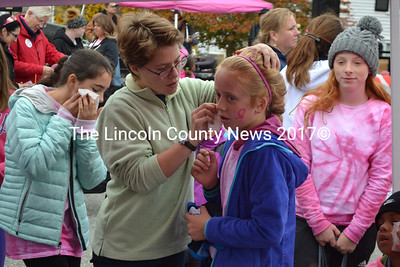 Skyler Houghton, of Newcastle, waits while a pink ribbon tattoo is applied to her cheek before the Making Strides Against Breast Cancer walk in Damariscotta on Sunday, Oct. 23. (Maia Zewert photo)