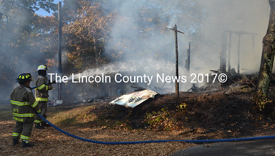 Firefighters hose down the remnants of a shed on North Dyer Neck Road in Newcastle on Wednesday, Oct. 19. (Maia Zewert photo)