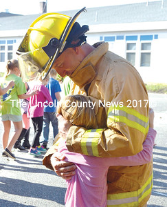 Bristol firefighter Leon MacCorkle gets a hug from his daughter, Leah MacCorkle, after a fire safety presentation at Bristol Consolidated School on Wednesday, Oct. 19. Members of the Bristol Fire Department talked about the importance of testing smoke detectors and establishing a place to meet in the event of a fire. (Maia Zewert photo)