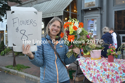 "Alicia Romac, of the Garden Club of Wiscasset, sells flowers in front of Treats at the Wiscasset Art Walk on Thursday, Sept. 29. ""We use the money for scholarships for local high school students going into earth sciences or environmental sciences,"" she said. (Christine LaPado-Breglia photo)"