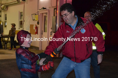 Bristol firefighter Daniel MacWalters watches as Joey Schnitzler sprays a fire hose at the Bristol Fire Department's Round Pond station on Monday, Oct. 31. The fire department had candy and hot cocoa for Halloween visitors. (Maia Zewert photo)