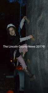 Avery Lawson, of Dresden, climbs the Camp Kieve climbing wall during the Damariscotta Police Department's annual trunk-or-treat event on Monday, Oct. 31. (Maia Zewert photo)