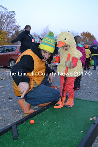 Topher Mallory offers his daughter, Flynn Mallory, putting tips during the Damariscotta Police Department's trunk-or-treat event. (Maia Zewert photo)