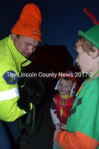 Nobleboro firefighter David Gallagher holds Wrangler, a puppy, for Thomas Roberts (center) and Matthew Roberts to pet at the Damariscotta Police Department's trunk-or-treat event on Halloween. (Maia Zewert photo)