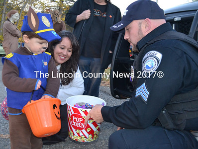 Nicholas Kupstas Jr., of Newcastle, collects candy from Sgt. Jason Warlick at the Damariscotta Police Department. (Maia Zewert photo)