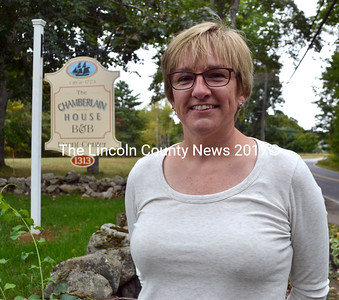 Shari Cunningham stands in front of the sign for The Chamberlain House B&B and Event Center at 1313 State Route 32 in Round Pond. (Maia Zewert photo)