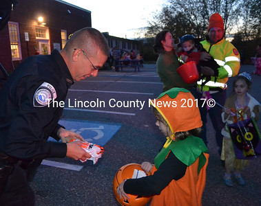 Damariscotta Reserve Officer Joel Seekins offers Brealynne Phelps candy during the department's annual trunk-or-treat event on Halloween, Monday, Oct. 31. (Maia Zewert photo)